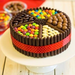 Large chocolate cake with chocolate fingers around the outside and sweets covering the top.