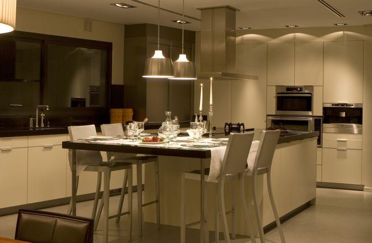 Cocina de la firma Leich, campana Pando y encimera de granito negro. Sillas de Emeco, diseño de Philippe Stark