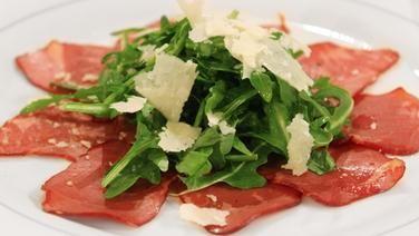 Carpaccio vom Bündnerfleisch mit Rucola und Parmesanhobeln serviert.