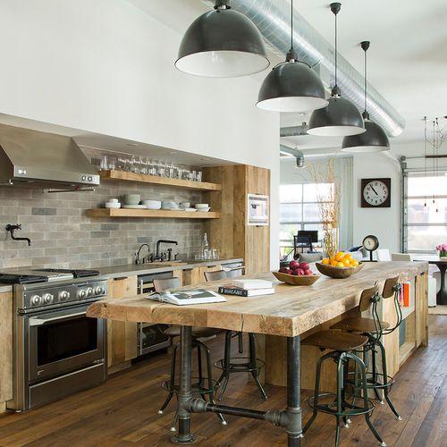 Foto de cocina de galera, urbana, grande, abierta, con armarios con paneles lisos, una isla, encimera de madera, salpicadero verde, electrodomésticos de acero inoxidable, puertas de armario de madera clara y suelo de madera oscura