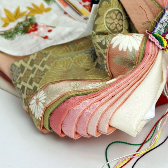 A close up of the layers of junihitoe a hina doll is dressed in.