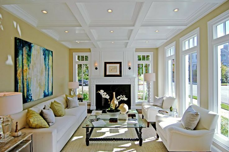 """Great living room decorated by Los Angeles home staging aficionado Meridith Baer. Wonderful blend of traditional and modern. Love the architecture of the room too. The bright white elegant coffered ceiling, the sleek fireplace mantel complete with decorative molding and paneling and the fab tall windows that wrap around the room....good and stylish """"bones"""". Love the decor too...white upholstered sofa and armchairs, the modern art, the turned wood and glass coffee table and all of the accents…"""