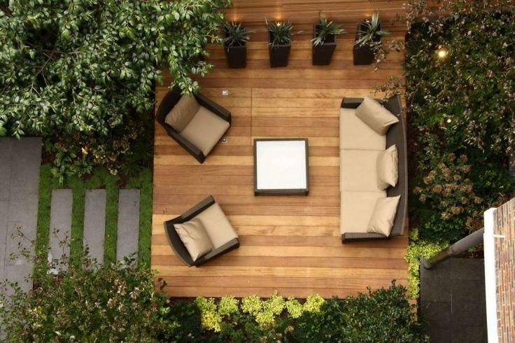terrasse en bois composite aménagée avec mobilier en rotin et plantes vertes