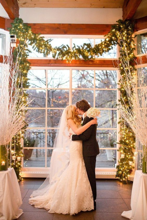 30 Winter Wedding Arches And Altars To Get Inspired: #9. Lit up fir garland used as an indoor wedding arch is a nice and simple idea for any winter celebration