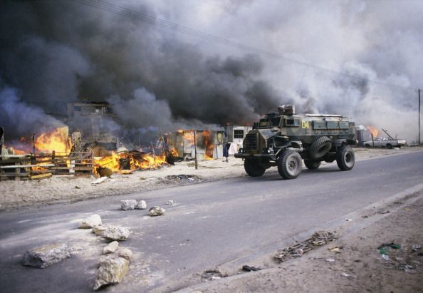 A South African security forces armored vehicle patrols by hundreds of burning houses in the KTC squatter community camp 09 June 1986 in Cape Town...