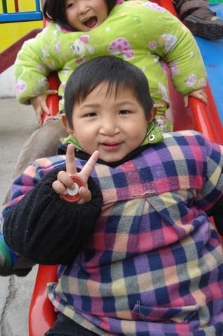 Jack, de nuestro programa de familias de acogida en Anhui, ha recibido un paquete especial este mes: fotos de su nueva familia! Está muy contento y tiene muchas ganas de conocerlos! En esta foto en el cole, Molly le va a pillar en el tobogán! :-)