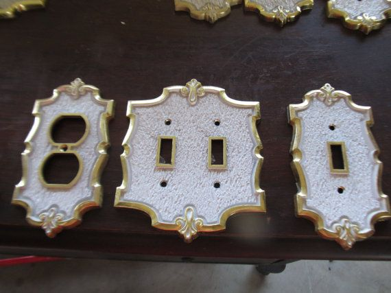 large lot of white and brass 1970s wall outlet covers on wall outlet id=66494