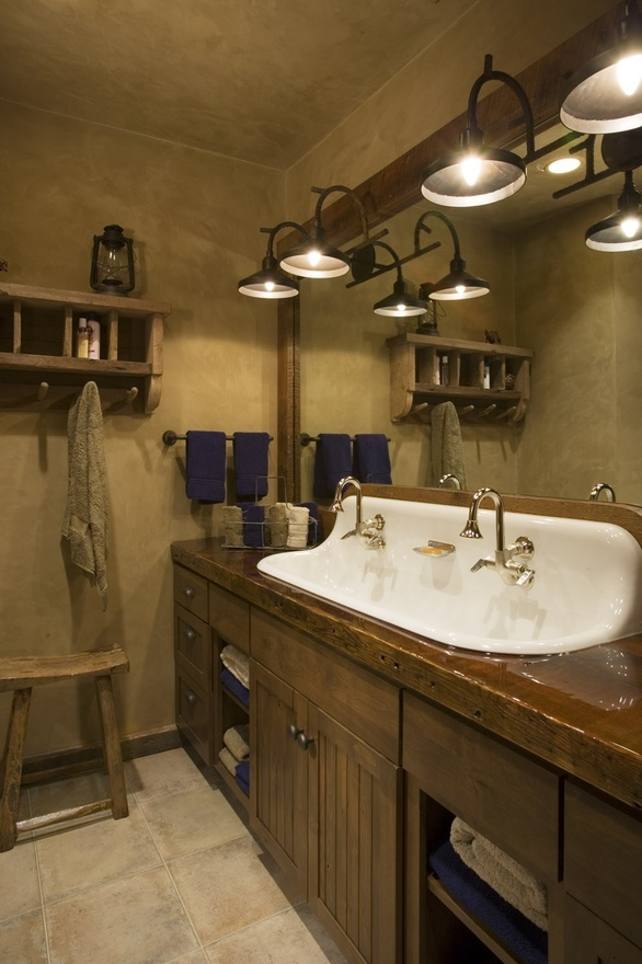 Castiron 4 sink.  Rustic mountain lodge bathroom. Wood countertop. Beadboard cabinet. Wall-mounted faucets.   Designed by Locati Interiors.