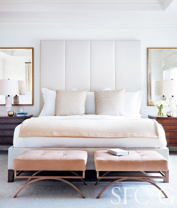 Bedroom with white walls, white headboard, antique brass mirrors, wood bedside tables, light pink ottoman and blanket, patterned pillows, and light carpeted floors