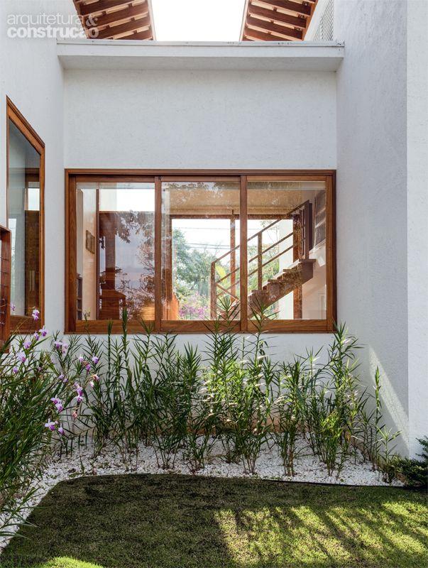 Casa incorpora árvore no deck e se beneficia de sua sombra_Aqui é o ponto em que a casa se divide em dois blocos, intermediados pelo hall de entrada, também envidraçado. As escadas conduzem aos quartos de cima e de baixo.