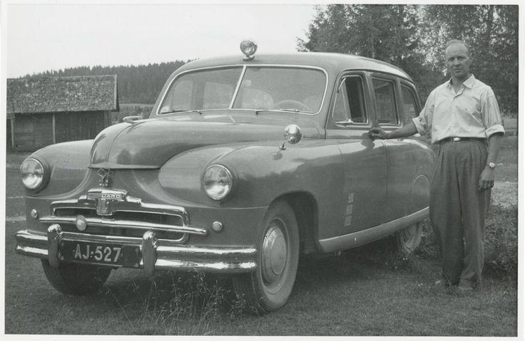 SKS:n auto ja vahtimestari Reino Rautavaara vuonna 1954. Standard Vanguard -merkkinen äänitysauto oli hankittu Oy Karl Fazer Ab:n lahjoittamilla varoilla. Kuva: 1954 (SKS, kirjallisuusarkisto).