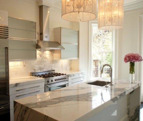 Gorgeous kitchen design with white string light chandeliers, frosted glass cabinets, and marble island & backsplash