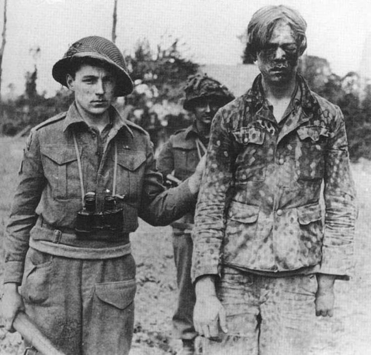 A Canadian soldier with a POW from the 12th SS Panzer 'Hitlerjugend' Division, Normandy, summer of 1944. The 12th SS was made up of fanatical 18-year-old volunteers freshly indoctrinated with Nazi ideals in the Hitler Youth, led by grizzled veterans of the brutal fighting on the eastern front. The 12th SS murdered 156 Canadian prisoners, mutilating several of the bodies by repeatedly running them over with tanks.