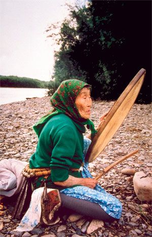 Wmen are Shamans in many cultures; here is Udegei Shaman Adikini holding her shaman's drum at a picnic on the river Khor;   photo by Kira Van Deusen
