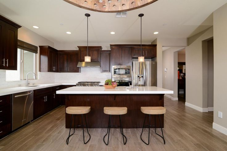 This minimalist kitchen features cherry wood cabinets and white countertops paired with stainless steel appliances. The spacious kitchen island offers a casual dining space with three neutral stools, while two pendant lights hang above.