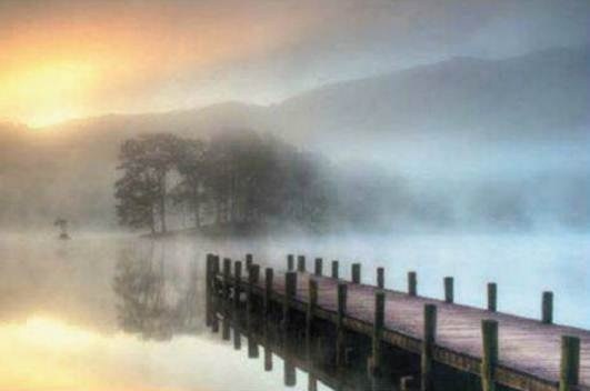 Lake District - Explore the heart of English - Misty Morning    'Lake bank on Coniston Water, this shot was taken early one morning as the mist was swirling on the water just as the sun was trying to break through.'