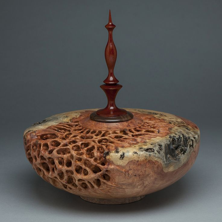 Turned and hand-carved wood vessel by Mark Doolittle. Woods are Amboyna Burl (vessel) and Walnut and African Padauk (finial).