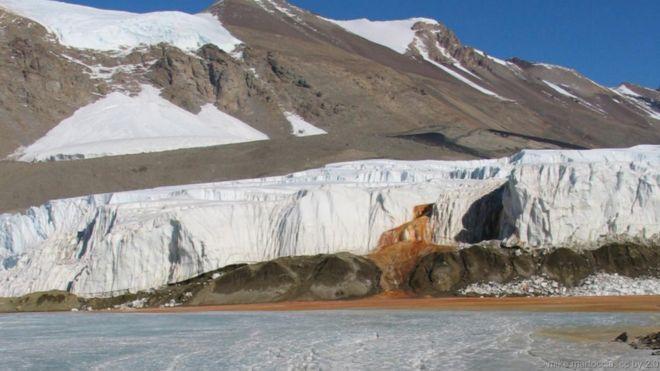 Thác máu, Nam Cực. Nằm trong những khối đông cứng ở vùng đông Nam Cực, một thác nước màu đỏ tươi chảy xuống từ các vết nứt của sông băng Taylor. Dòng nước chảy ra từ một cái hồ siêu mặn vốn đã nằm dưới sông băng này suốt hai triệu năm. Khi dòng nước giàu chất sắt chảy ra, sắt phản ứng với ô-xi trong không khí tạo thành chất rỉ sét, và do đó khiến cho dòng thác nước mang sắc đỏ rực rỡ. Cộng đồng vi khuẩn có từ cổ xưa sinh sống trong hồ rất có thể sẽ đem lại cho con người những manh mối…