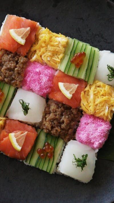 Recipe with video instructions: How to make a Mosaic Block Sushi. Ingredients: 280 cc rice, 260 cc water, 4 teaspoons sake, Sushi rice seasonings:, 40 cc rice vinegar, 2 teaspoons sugar, 1 teaspoon salt, Sushi fillings and toppings:, 3 sheets nori, cut in half, 2 slices smoked salmon, 3 thinly sliced lemon, 1/2 cucumber, thinly sliced, Ikura (salmon roe), Sakura denbu (pink fish flakes), 1 small fillet of squid (sashimi quality), 1 pirella leaf, cut into thin strips, Seasoned ground chic...