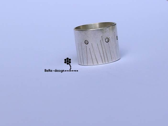 Spring meadow with daisies captured in a silver ring and small zirconia stones.