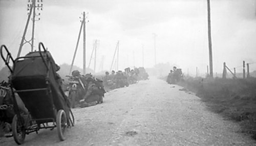 D-Day, 6 June 1944: Canadian infantry wait in ditches with their bicycles as men of the 48th Royal Marine Commando take cover from mortar fire on the roadside near St Aubin sur Mer. On the first day, the British and Canadian divisions made rapid advance inland but failed to take Caen, which had been their initial objective.
