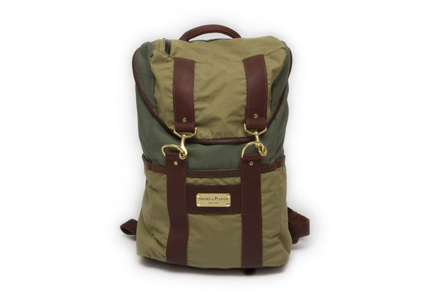 """Our signature piece and the """"go to"""" bag in military – the rucksack! Two-tone olive and forest green. A beautifully hand-crafted unisex backpack for all occasions. Made from gortex sleeping bag bivies, laundry bags and accented with local Colorado leather. Includes padded shoulder straps, a camo cinch to ensure your gear will stay dry, and a waterproof laptop sleeve."""