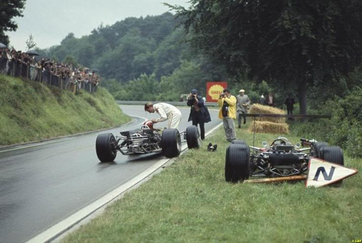 Rouen-Les-Essarts, 1968. Graham Hill offers his helmet visor to team mate Jo Siffert after Hills car had broken down.