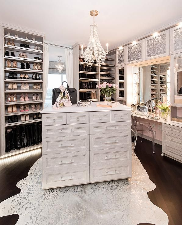 Glamorous walk in closet features a white metallic cowhide rug placed on dark stained wood floors beneath a light gray island illuminated by a white beaded chandelier.