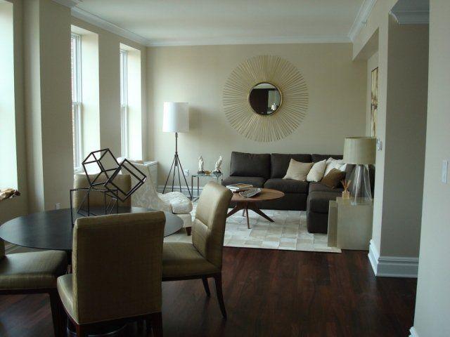 un canapé marron sombre et des chaises en beige dans le salon