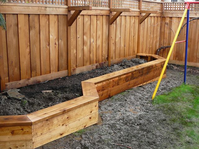 Raised planter box along fence that doubles as a bench, with brackets for hanging plants. Love this idea!