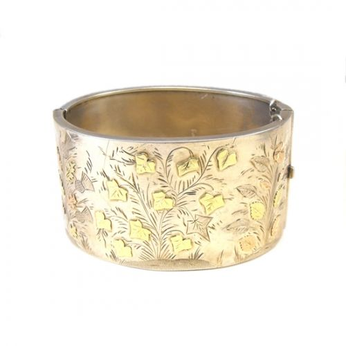 Gorgeous English Victorian sterling silver bangle, hallmarked Chester 1881. Decorated with engravings of ivy and thistles with green and rose gold leaves.