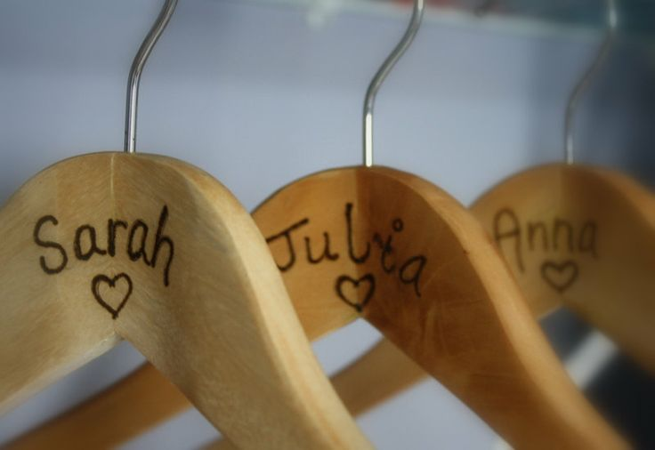 Write wedding party's names on the hangers in Sharpie, or let dad or groom burn them into the wood