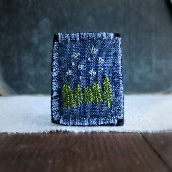 This hand embroidered textile art brooch has a star filled night sky over a stand of evergreens, it is stitched on hand dyed navy blue linen and has a dark blue wool felt backing. Size: 1 1/2 inches wide by 2 inches tall I do my best to get the colors as true to life as possible but please keep in mind that the colors may vary from monitor to monitor. You can find more of my brooches here: http://www.etsy.com/shop/Sidereal?section_id=7924086 or Click here to go back to my shop home page:...