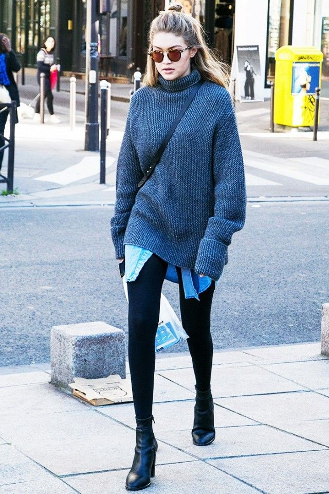 Gigi Hadid wears a denim shirt, turtleneck sweater, leggings, and ankle boots