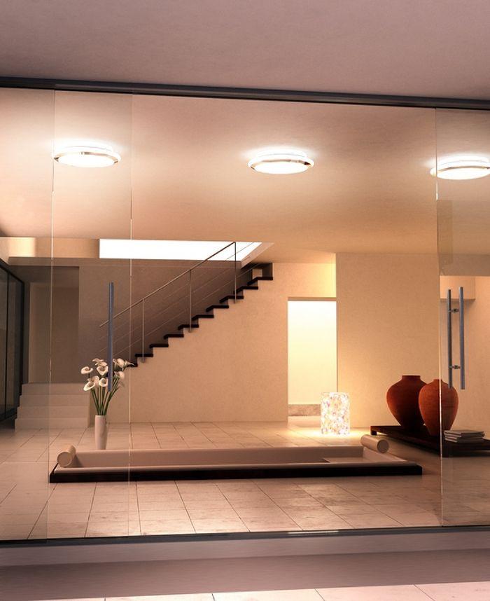 Zaokrąglona lampa sufitowa na świetlówkę kompaktową 2D, wykonana z opalowego szkła, wykończona ozdobnie pierścieniem w kolorze chromowym.