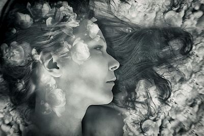 Annica Mari Albin - Floating among flowers. A black and white photograph of a woman lying on a bed of flowers.
