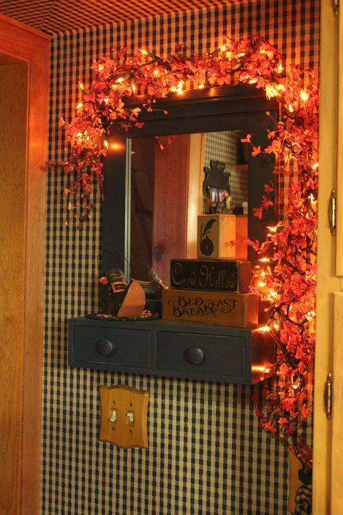 """Silk leaves, mini lights wrapped around a mirror or picture. Nice alternative for """"mantle"""" decor"""
