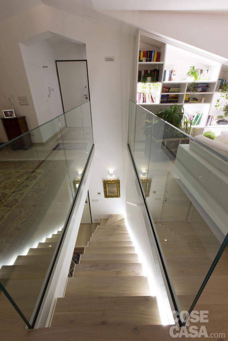La scala, realizzata su misura, è leggermente scostata dal muro e illuminata lateralmente da una striscia di luci a led che ne aumenta l'effetto sospeso. Il parquet riveste sia le alzate sia le pedate creando l'effetto di una pavimentazione continua.