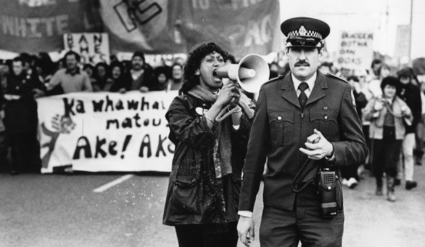 here we see a woman shouting in an officers ear probably shouting a chant about apartheid or anti tour