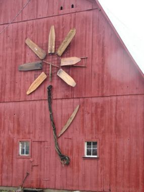 antique ironing boards create the flower design on the side of a barn