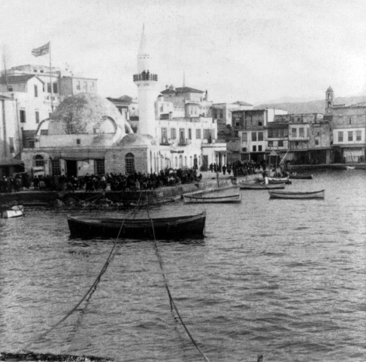 Χανιά, 1897, βάρκες στο λιμάνι. Πίσω από το Κιουτσούκ Χασάν τζαμί η σημαία του βρετανικού προξενείου.