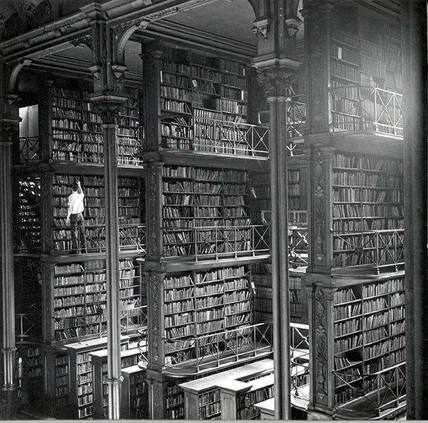 Человек просматривает книги в старой городской библиотеке Цинциннати. Библиотека была снесена в 1955 году