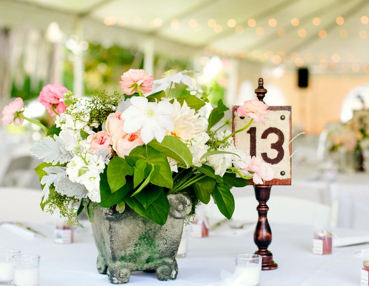 outdoor receptions tables are set under a tent with twinkle lights.  garden inspired centerpieces of peach juliette garden roses,pink ranunculus, white clematis, white stock, dusty miller, seeded eucalyptus and lemon leaf are set in mossed concrete pots.