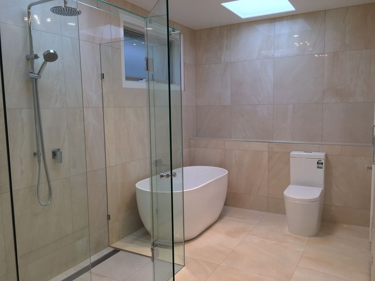 When less is more.   This white bath makes the place feels light and bright with the frameless shower that opens up the whole space.