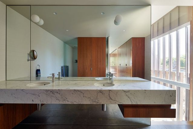 In the bathroom, a marble vanity appears to float against a full-height mirrored wall.