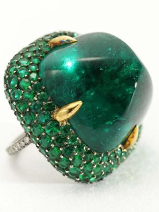 JAR: A 39.74 carat sugarloaf cabochon emerald set within a bombé pavé-set emerald surround, mounted in silver and gold.  Formerly the property of Ellen Barkin.