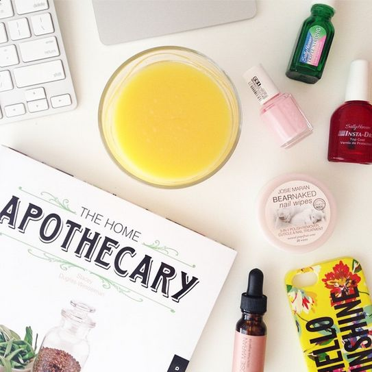 how to style instagram photos like a blogger: good lighting - home apothecary book, bright yellow candle + iphone case with nail polish and essential oils