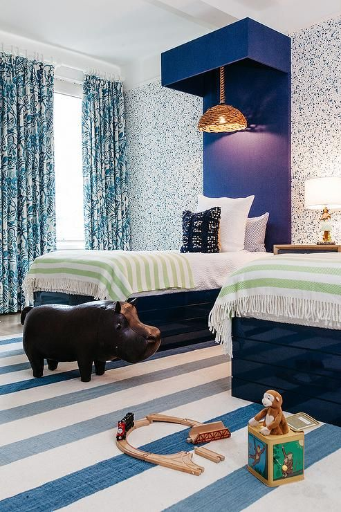 Shared boys bedroom features wall clad in navy blue paint