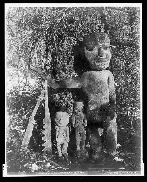 Doctor's Grave, Chilkat. c. 1895 Tlingit sculpture Klukwan  Alaska Natives--Southeast.  Gow-ge-a-deh-Iktuk grave; close-up of one large, two small human figure totems; two other carved objects. Alaska's Digital Archives