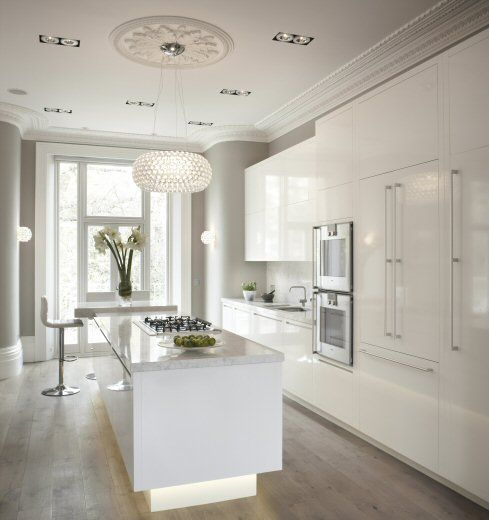 Wooden floors, gloss white furniture and marble tops.